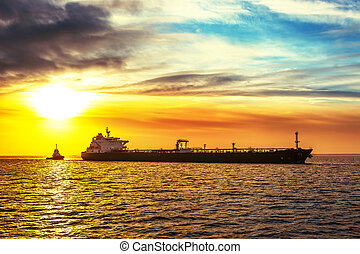 Tanker and tug - Tugboat pulling the tanker at sea in the...