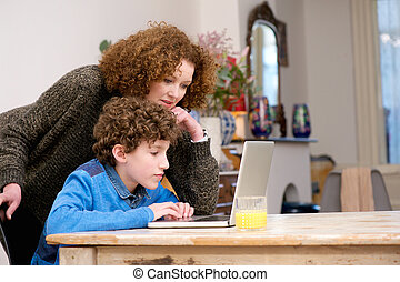 Woman helping little boy using computer at home