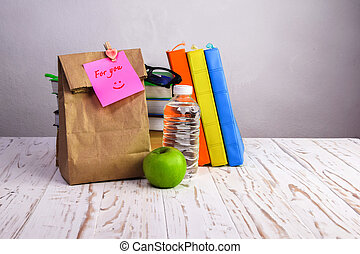paper  lunch bag  with apple,water and books  on desk with post-it note