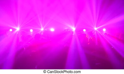 People dancing during rave party with stroboscopic pink...