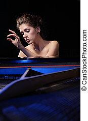 woman playing piano - A beautiful young woman playing piano...