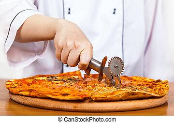 chef cuts the pizza