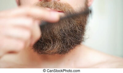 Man combing his mustac - Care beard - man combing his...