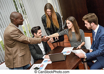 Business people shaking hands, finishing up a meeting -...