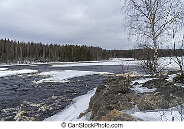 Rock ate the rapids in winter. Karelia, Russia.