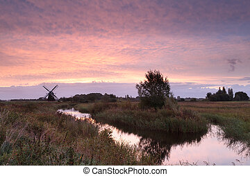 Dutch windmill by river at sunrise