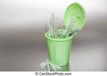 Green Garbage can with medical waste Syringes protrude out...