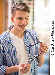 Sunglasses store - Young man is choosing sunglasses at the...