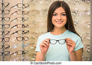 Oprician store - Young woman is choosing a glasses in...