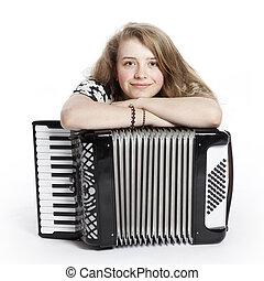 smiling teenage girl on the floor of studio with accordion...