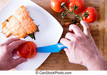 Chef plating up a gourmet salmon dinner