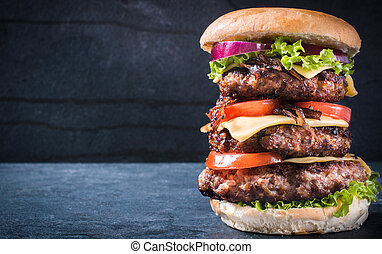 Triple American burger with cheese and grilled...