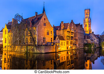 Bruges, Belgium at dusk. - Historic medieval buildings along...