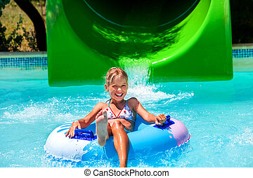 Child on water slide at aquapark. Summer holiday. Green and...