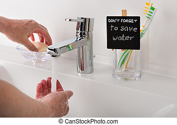 Reminder to save water in the bathroom. Detail shot of the...