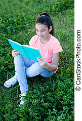 Little girl with blue eyes reading a book outside