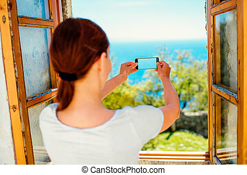 Photographing sea from the window - Young woman...