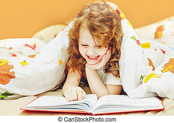 Little girl reading a book in bed before going to sleep....
