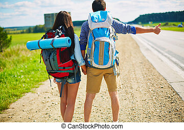 Hitch-hikers - Young man and woman with rucksacks...