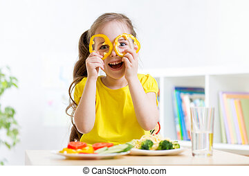smiling child eating in kindergarten - child girl eats vegan...