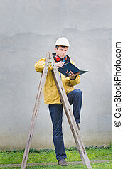 Engineer leaned on ladder - Engineer in safety suit leaned...