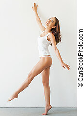 Confident t in her perfect body. Full length of attractive young woman in white tank top and panties posing while standing against white background