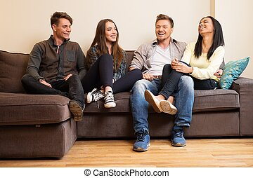 Cheerful multi-ethnic friends sitting on a sofa