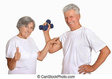 Portrait Of A Senior Couple Exercising With Dumbbells in a...