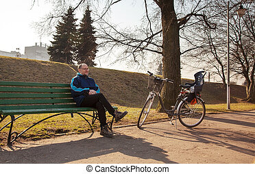 elderly man sitting on a bench near his bicycle in a city park