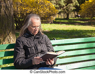 haired elderly man reading a book sitting on a bench in city...