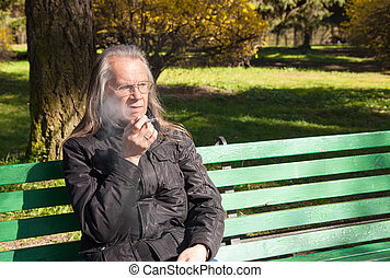 elderly gray-haired man in glasses smoking a cigarette in...