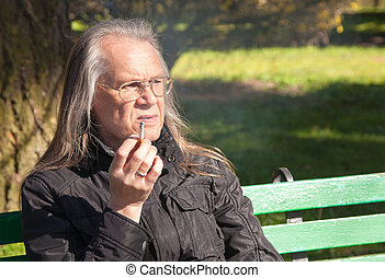 elderly gray-haired man in glasses smoking a cigarette -...