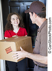 Receiving Home Delivery - Young woman receives a home...