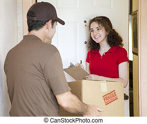 Young Woman Signs for Delivery - Young woman signs for a...