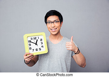 Happy asian man holding big clock and showing thumb up over...