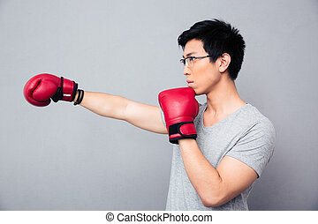 Asian man fighting in boxing gloves