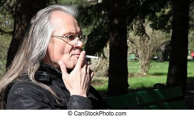 elderly man smoking a cigarettei - elderly gray-haired man...