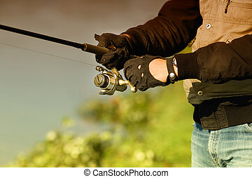 Fishing rod - Close up of male hands in gloves holding...