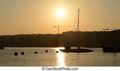 The timelaps of sunset and view on Sliema and sail yacht...