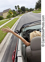 Young Woman Driving Convertible Car With Hand In The Air - A...