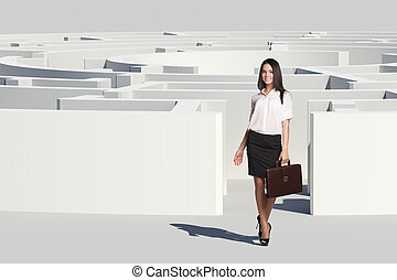 Businesswoman with suitcase looking at camera, near...
