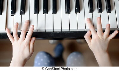 Child learns to play the piano
