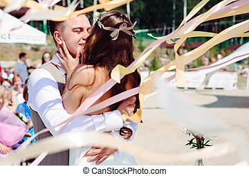 Wedding couple dancing and kissing in flying ribbons...