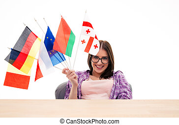 Happy young woman sitting at the table with international flags
