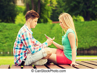 couple with smartphones sitting on bench in park - summer,...