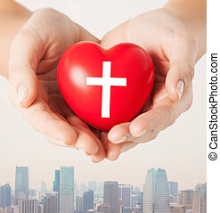 close up of hands holding heart with cross symbol -...