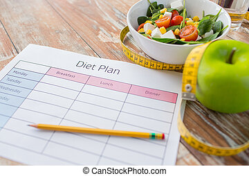 close up of diet plan and food on table - healthy eating,...