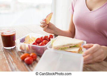 close up of woman with food in plastic container - healthy...