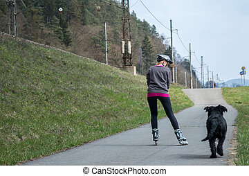 Woman is skating on rollerblades beside her dog outdoors -...