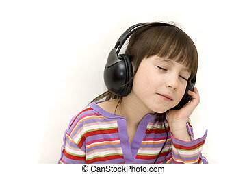 little girl listening to music with headphones on white...